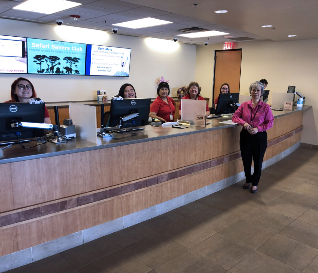 ASCU Team Members behind counter, with a single female standing in front of the counter at ASCU's Main Branch