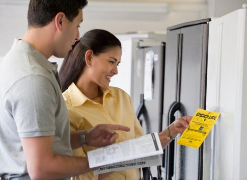 Couple looking at energy efficiency ratings on appliances